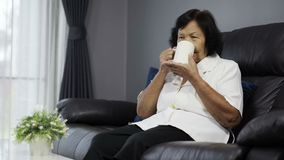 Mujer mayor que bebe una taza de agua almacen de metraje de vídeo