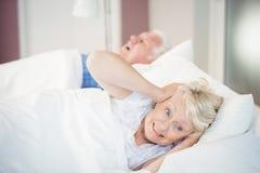 Mujer mayor que bloquea los oídos mientras que hombre que ronca en cama Imagen de archivo libre de regalías