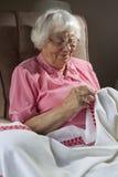 Mujer mayor que borda Imagenes de archivo