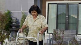 Mujer mayor que camina con el caminante almacen de metraje de vídeo