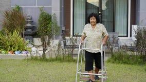 Mujer mayor que camina con el caminante metrajes