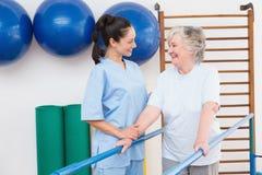 Mujer mayor que camina con las barrases paralelas con el terapeuta Fotos de archivo libres de regalías