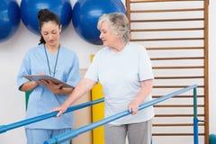 Mujer mayor que camina con las barrases paralelas con el terapeuta Foto de archivo libre de regalías