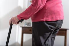 Mujer mayor que camina con un bastón foto de archivo