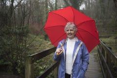 Mujer mayor que camina en la lluvia Imagenes de archivo