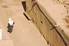 Mujer mayor que camina en una calle vacía en Bukhara Imagen de archivo libre de regalías