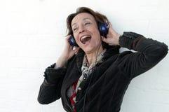 Mujer mayor que canta con los auriculares Imagenes de archivo