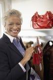 Mujer mayor que celebra el monedero en la tienda Foto de archivo