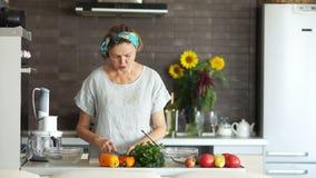 Mujer mayor que cocina la comida en la cocina casera El ama de casa corta los pepinos Interior moderno, brillante de la cocina, v almacen de video