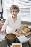 Mujer mayor que cocina la sopa en cocina Imagenes de archivo