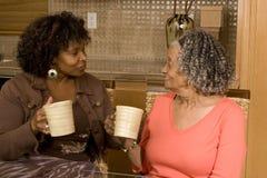 Mujer mayor que come café con su hija imagenes de archivo