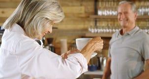 Mujer mayor que come café en el contador 4k del café almacen de video
