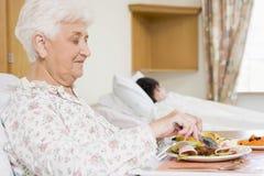 Mujer mayor que come el alimento del hospital Imagen de archivo