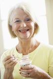 Mujer mayor que come el yogur Imagenes de archivo