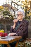 Mujer mayor que come la taza de café Foto de archivo libre de regalías