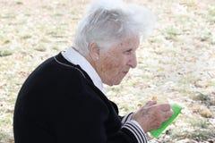 Mujer mayor que come la torta Imagen de archivo libre de regalías