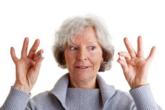 Mujer mayor que compara dos píldoras Fotografía de archivo