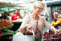 Mujer mayor que compra frutas y verduras frescas en el mercado local foto de archivo