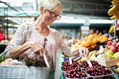 Mujer mayor que compra frutas y verduras frescas en el mercado local fotos de archivo