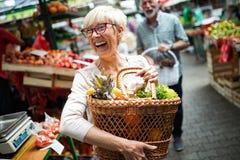 Mujer mayor que compra frutas y verduras frescas en el mercado local imágenes de archivo libres de regalías
