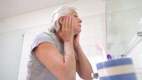 Mujer mayor que comprueba la piel en espejo del cuarto de baño almacen de metraje de vídeo