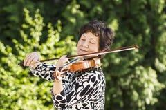 Mujer mayor que concentra mientras que juega música al aire libre Fotos de archivo libres de regalías