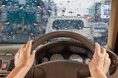 Mujer mayor que conduce un coche lentamente en la ciudad, día lluvioso imagen de archivo libre de regalías