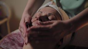 Mujer mayor que consigue el tratamiento en balneario de la belleza almacen de video