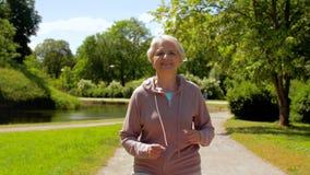 Mujer mayor que corre a lo largo de parque del verano almacen de metraje de vídeo