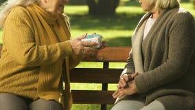 Mujer mayor que da el presente al amigo, deseando feliz cumpleaños, sorpresa agradable almacen de video