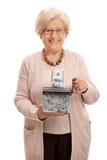 Mujer mayor que destruye un billete de banco del dólar en una trituradora de papel Fotos de archivo