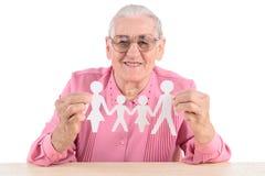 Mujer mayor que detiene a la familia de papel Foto de archivo