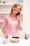 Mujer mayor que disfruta de la bebida caliente mientras que en el teléfono imagen de archivo libre de regalías