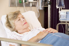 Mujer mayor que duerme en cama de hospital Imagen de archivo libre de regalías