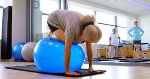 Mujer mayor que ejercita con el ejercicio de la bola 4k metrajes