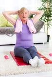 Mujer mayor que ejercita en el gimnasio casero Imágenes de archivo libres de regalías