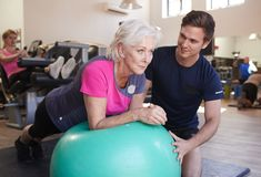 Mujer mayor que ejercita en la bola suiza que es animada por el instructor personal In Gym fotos de archivo libres de regalías