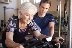 Mujer mayor que ejercita en la máquina de ciclo que es animada por el instructor personal masculino In Gym foto de archivo libre de regalías