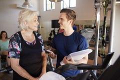 Mujer mayor que ejercita en la máquina de ciclo que es animada por el instructor personal masculino In Gym fotografía de archivo libre de regalías