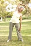 Mujer mayor que ejercita en parque Fotos de archivo libres de regalías