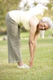 Mujer mayor que ejercita en parque Imágenes de archivo libres de regalías