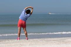 Mujer mayor que ejercita en una playa Imagen de archivo libre de regalías
