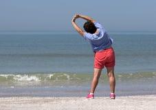 Mujer mayor que ejercita en una playa Foto de archivo libre de regalías