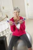 Mujer mayor que ejercita mientras que mira DVD de la aptitud en la televisión Fotografía de archivo