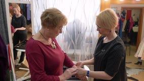 Mujer mayor que elige la pulsera en tienda de la moda almacen de metraje de vídeo