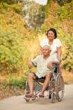 Mujer mayor que empuja su hasband discapacitado en la silla de ruedas Imagen de archivo libre de regalías