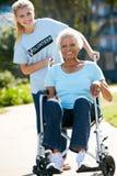 Mujer mayor que empuja voluntaria en silla de ruedas Fotos de archivo