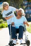 Mujer mayor que empuja voluntaria en silla de ruedas Imagen de archivo
