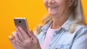 Mujer mayor que enrolla el uso y la cámara sonriente, redes sociales del smartphone metrajes