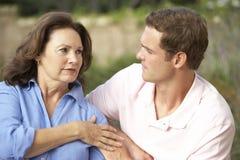Mujer mayor que es confortada por Adult Son Foto de archivo libre de regalías